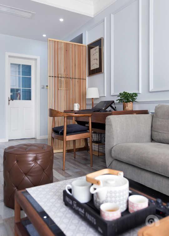 地面撞色木地板,墙面浅蓝色的乳胶漆,定下客厅